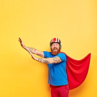 Imagem de um cara barbudo surpreso e feliz usando uma fantasia especial, vem na festa, faz gesto de defesa