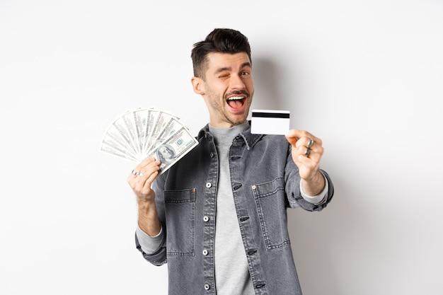 Imagem de um cara bonito segurando notas de dólar, mas sugerindo usar cartão de crédito de plástico, sorrindo amigável para a câmera, em pé sobre fundo branco.