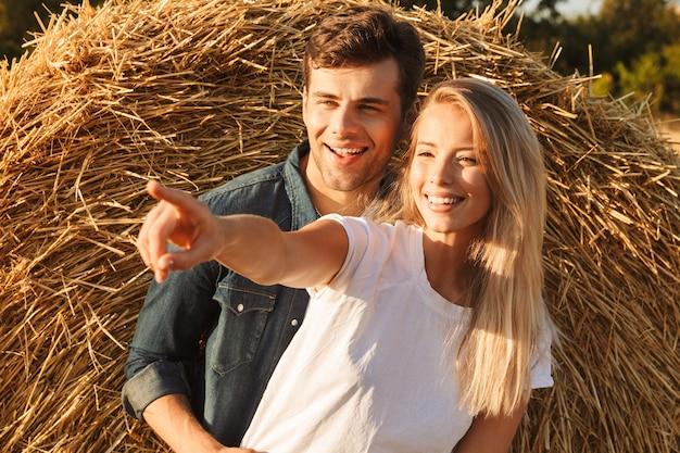 Imagem de um casal alegre, homem e mulher, caminhando em um campo dourado após a colheita e perto de um grande palheiro