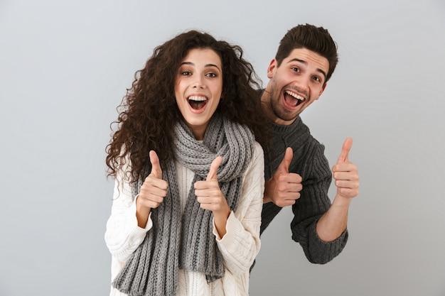 Imagem de um casal alegre, homem e mulher, rindo e mostrando os polegares para cima, isolada sobre uma parede cinza