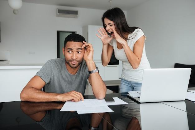 Imagem de um casal apaixonado, discutindo sobre as contas domésticas em casa. mulher gritando para o homem enquanto o homem olha de lado.