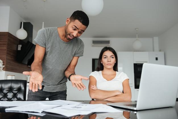 Imagem de um casal apaixonado, discutindo sobre as contas domésticas em casa. mulher sério, desvie o olhar. homem gritando para a mulher enquanto segura os documentos.