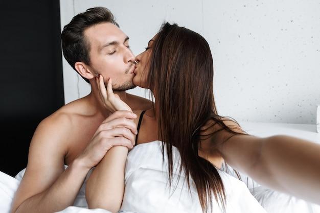 Imagem de um casal apaixonado, homem e mulher, tirando uma foto de selfie juntos, enquanto se beijam na cama em casa ou em um apartamento de hotel
