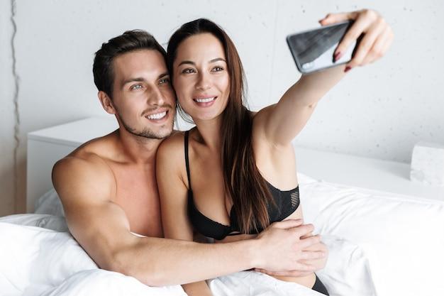 Imagem de um casal caucasiano homem e mulher tirando uma foto de selfie juntos, enquanto está deitado na cama em casa ou apartamento de hotel