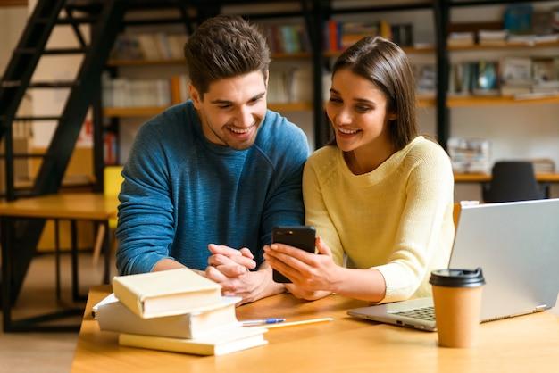 Imagem de um casal de amigos de jovens estudantes na biblioteca estudando, conversando usando telefone celular.