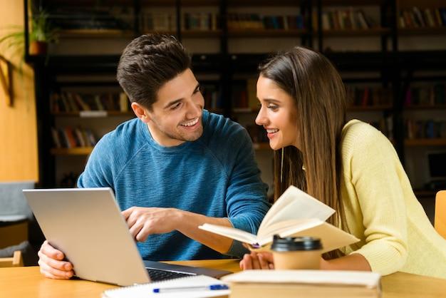 Imagem de um casal de amigos de jovens estudantes na biblioteca fazendo lição de casa, estudando ler e usando o computador portátil.