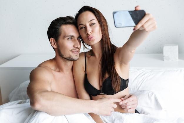 Imagem de um casal europeu, um homem e uma mulher, tirando uma foto de selfie juntos, enquanto está deitado na cama em casa ou apartamento de hotel