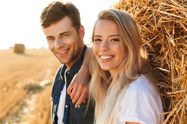 Imagem de um casal romântico, homem e mulher, caminhando em um campo dourado e em pé perto de um grande palheiro