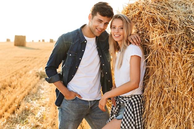 Imagem de um casal sorridente, caminhando em um campo dourado e perto de um grande palheiro