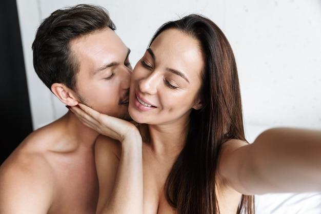 Imagem de um casal sorridente tirando uma foto de selfie juntos, deitado na cama em casa ou em um apartamento de hotel
