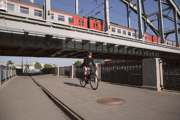 Imagem de um ciclista passando sob uma ponte ferroviária com um trem