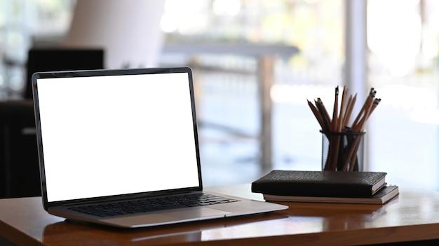 Imagem de um computador tablet com tela em branco, artigos de papelaria e cadernos na mesa de madeira.
