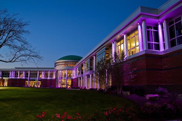 Imagem de um edifício moderno com muitas janelas no crepúsculo iluminada em roxo