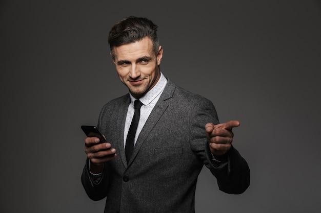 Imagem de um empregador satisfeito, vestido com uma fantasia de negócios, segurando um telefone celular e apontando o dedo na copyspace, isolada sobre uma parede cinza