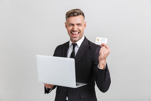 Imagem de um empresário adulto positivo em um terno formal regozijando-se enquanto segura o laptop e o cartão de crédito isolados