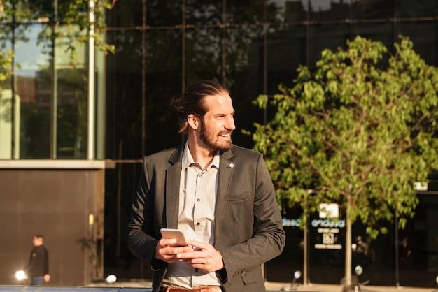 Imagem de um empresário barbudo de 30 anos em um terno formal segurando um smartphone e olhando para o lado, em frente a um prédio de escritórios ou centro comercial em área urbana