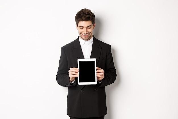 Imagem de um empresário bem parecido em um terno preto, olhando para a tela do tablet digital e mostrando um anúncio, em pé contra um fundo branco
