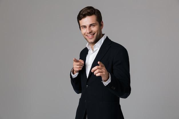 Imagem de um empresário de sucesso na casa dos 30 anos em um terno formal apontando o dedo para você, isolada sobre uma parede cinza