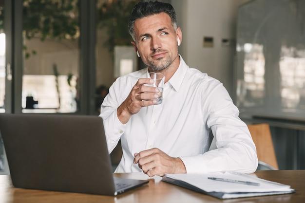 Imagem de um empresário europeu dos anos 30 vestindo camisa branca e fone de ouvido sentado à mesa no escritório e bebendo água de vidro enquanto trabalhava no laptop