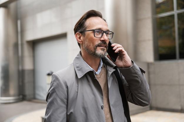 Imagem de um empresário satisfeito em óculos, falando ao celular em pé perto de um prédio comercial na rua da cidade