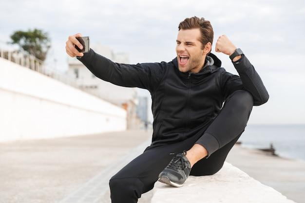 Imagem de um esportista alegre dos 30 anos em uma roupa esportiva preta, tirando uma foto de selfie no celular enquanto está sentado no calçadão à beira-mar
