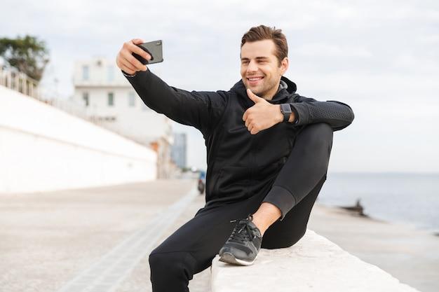 Imagem de um esportista de 30 anos satisfeito em uma roupa esportiva preta, tirando uma foto de selfie no celular enquanto está sentado no calçadão à beira-mar