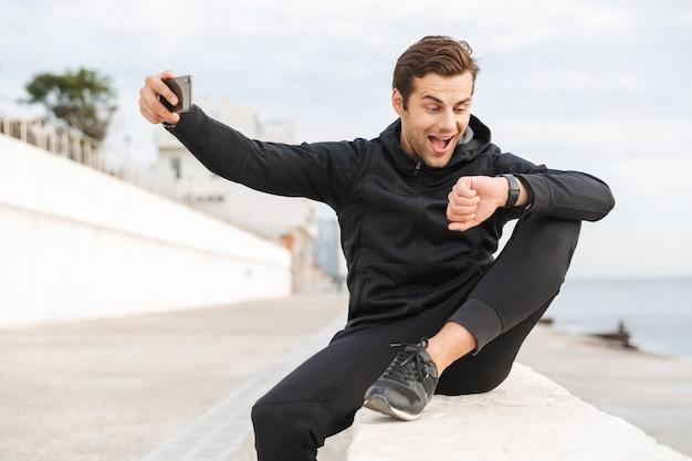 Imagem de um esportista feliz dos 30 anos em uma roupa esportiva preta, tirando uma foto de selfie no celular enquanto está sentado no calçadão à beira-mar