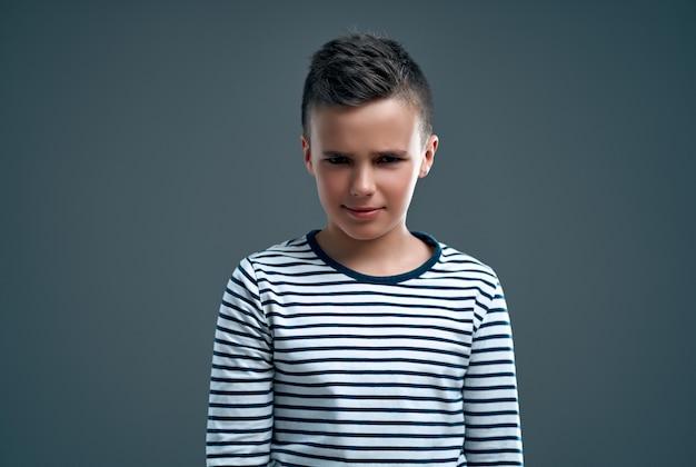 Imagem de um garoto descontente garoto posando isolado sobre uma parede cinza.