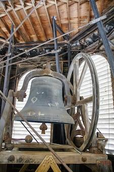 Imagem de um grande sino de metal em uma torre com mecânica e engrenagens