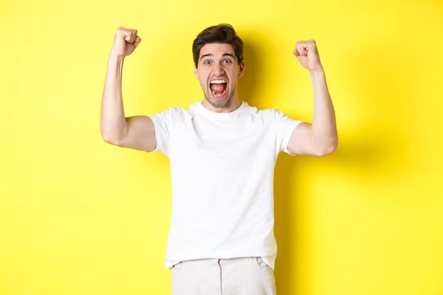Imagem de um homem animado vencendo, levantando as mãos e comemorando, triunfando e torcendo pelo time, em pé sobre fundo amarelo. copie o espaço