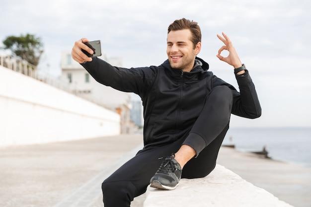 Imagem de um homem atlético de 30 anos em uma roupa esporte preta, tirando uma foto de selfie no celular enquanto está sentado no calçadão à beira-mar