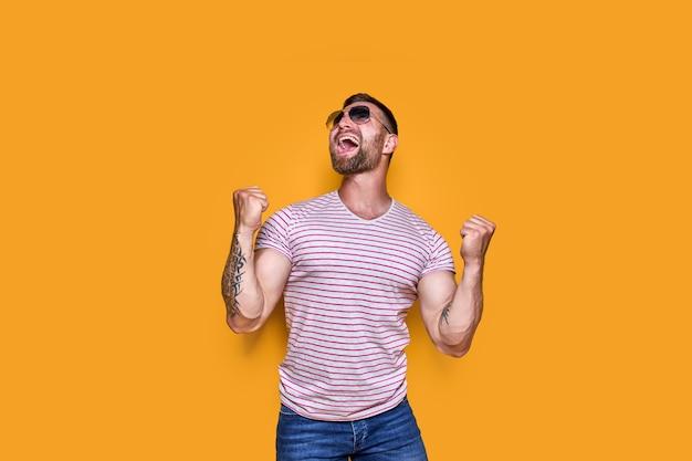 Imagem de um homem barbudo animado usando óculos escuros fazendo gesto de vencedor isolado com fundo amarelo