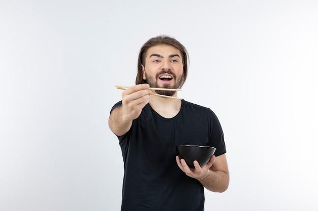 Imagem de um homem barbudo segurando uma tigela com pauzinhos sobre uma parede branca.