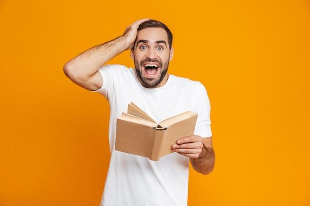 Imagem de um homem bigodudo de 30 anos em uma camiseta branca segurando e lendo um livro, isolado