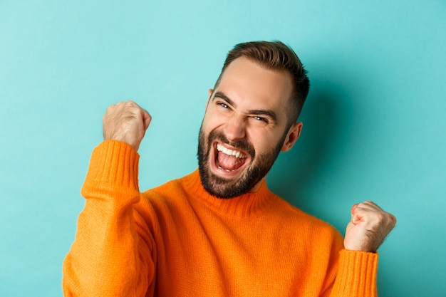 Imagem de um homem bonito aliviado sentindo-se satisfeito, regozijando-se com a vitória ou conquista