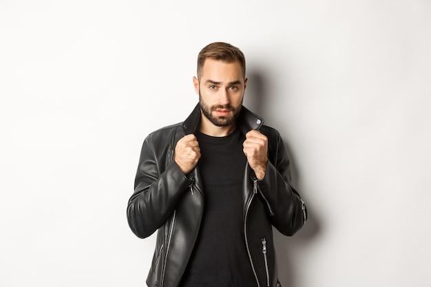 Imagem de um homem bonito e confiante vestindo uma jaqueta de couro de motoqueiro, em pé