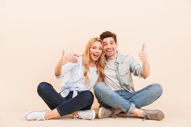 Imagem de um homem bonito e uma linda mulher se abraçando enquanto está sentado no chão com as pernas cruzadas e mostrando os polegares para cima, isolado sobre uma parede bege