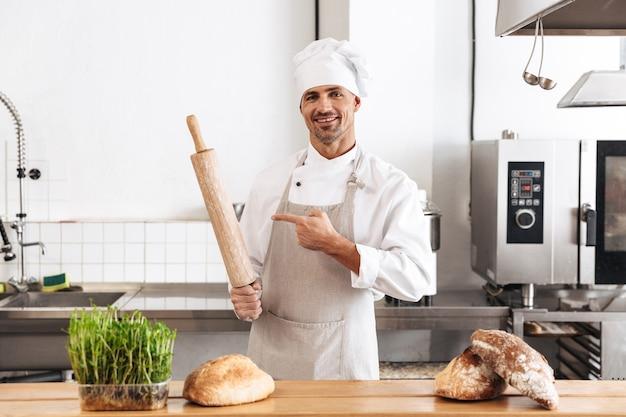 Imagem de um homem bonito padeiro em uniforme branco sorrindo, em pé na padaria com pão na mesa