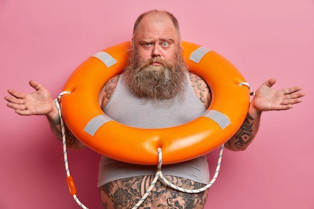 Imagem de um homem com excesso de peso intrigado abre as mãos, posa com uma bóia salva-vidas inflada, usa uma camiseta subdimensionada, barriga gorda tatuada saindo dela, indo nadar no mar, isolada na parede rosa