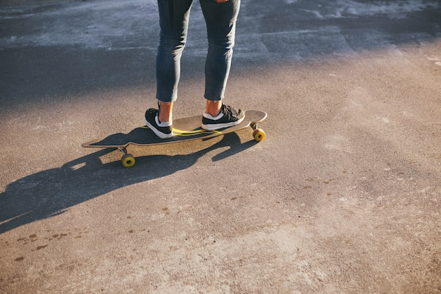Imagem de um homem com longboard indo na estrada