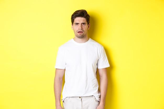 Imagem de um homem confuso e intrigado que não consegue entender algo, franzindo a testa e parecendo chocado, em pé sobre um fundo amarelo.