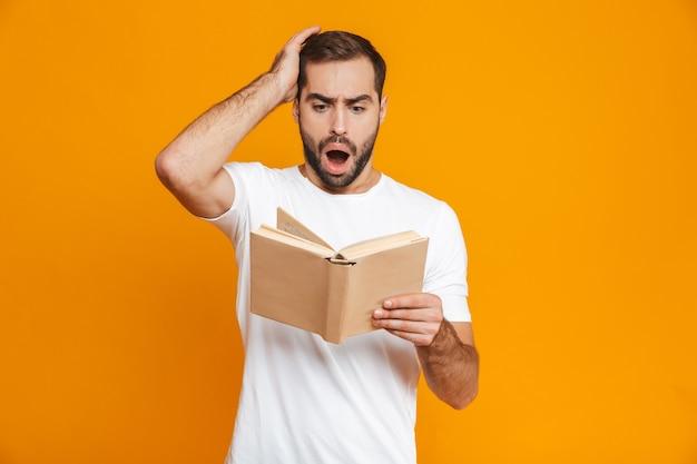 Imagem de um homem de 30 anos preocupado, com uma camiseta branca, segurando e lendo um livro, isolado