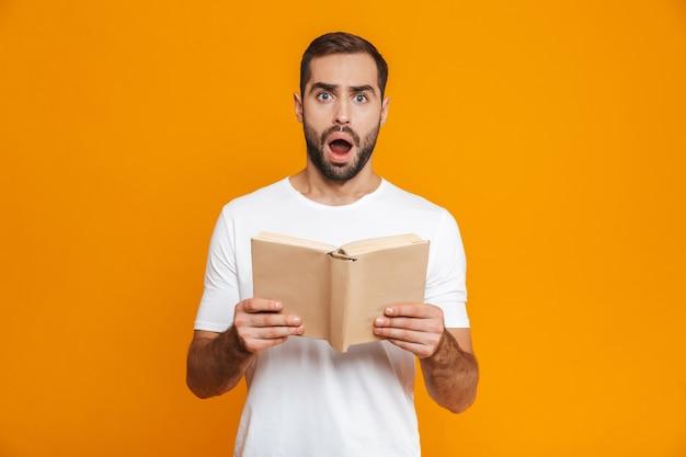 Imagem de um homem de 30 anos surpreso em uma camiseta branca segurando e lendo um livro, isolado