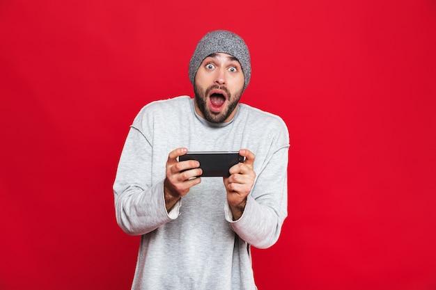 Imagem de um homem de 30 anos surpreso segurando um smartphone e jogando videogame, isolado