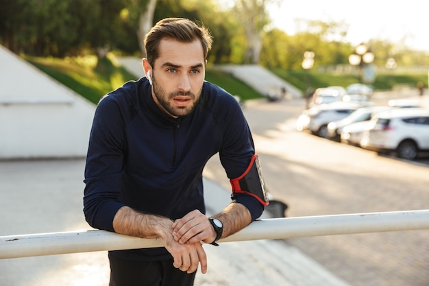 Imagem de um homem de esportes fortes jovem bonito posando ao ar livre no local do parque natural, ouvindo música com fones de ouvido.