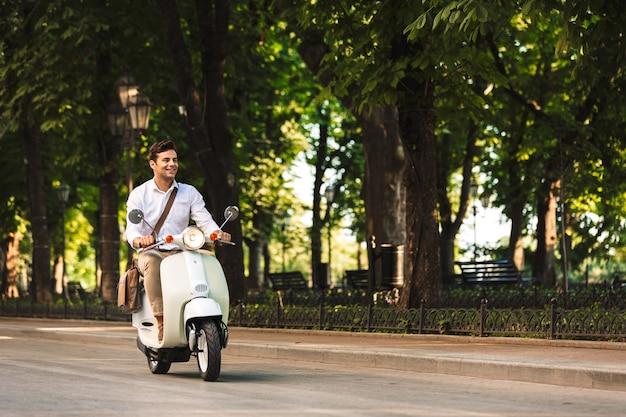 Imagem de um homem de negócios jovem bonito caminhando ao ar livre na scooter.