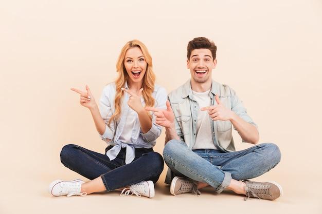 Imagem de um homem e uma mulher caucasianos de dois amigos sentados no chão com as pernas cruzadas e apontando os dedos de lado para copyspace, isolado sobre uma parede bege