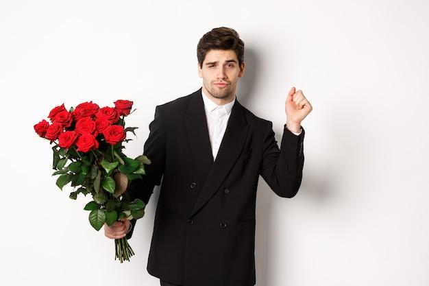 Imagem de um homem elegante e atrevido em um terno preto, parecendo confiante e segurando o buquê de rosas vermelhas, tendo um encontro romântico, de pé contra um fundo branco.