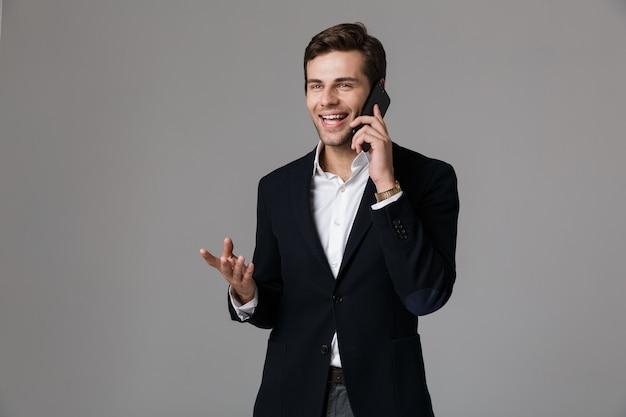 Imagem de um homem feliz dos 30 anos em um terno de negócio falando em um smartphone preto, isolada sobre uma parede cinza