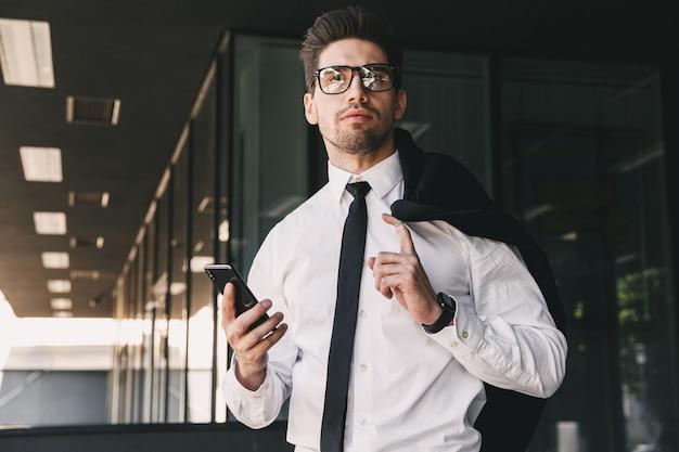 Imagem de um homem formal, vestido com um terno formal, do lado de fora do prédio de vidro, com uma jaqueta sobre o ombro e segurando um telefone celular